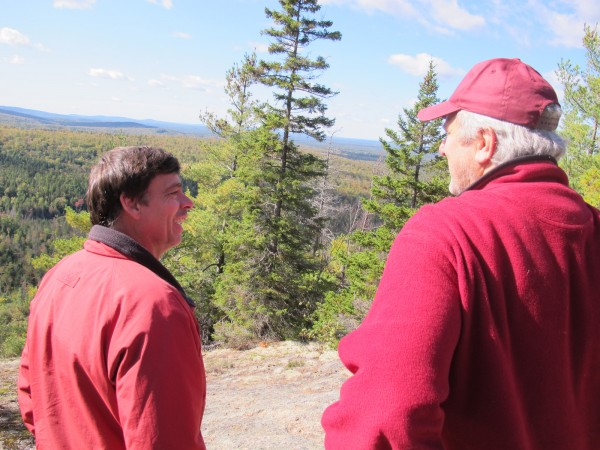 Amherst selectman Phil Deckers (left) chats with Airline Community School principal Andy Bryan at the summit of Bald Bluff Mountain in Amherst during a ceremony to mark the formation of the Amherst Mountains Community Forest held Thursday.