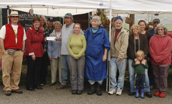 The Bangor Savings Bank Foundation recently awarded a grant to the Belfast Farmers Market. Marking the occasion are bank officials, farmers market vendors and others. They are (from left) Eric Rector, Kathy Reynolds and Amy Bowen from the bank; Delmar Levesque and Lou Chamberland of Waterfall Arts; and vendors Kevin Weiser, Marcia Ferry, Sandy Spinney, Anne Saggese, John Spinney, Lynn Cottrell and Owen, Jessica Farrar, Ken Lamson, Caitlin Hunter. The bank foundation recently awarded a grant to the farmers market.