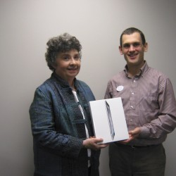 Big Brothers Big Sisters of Midcoast Maine CEO Alex Gaeth (right) presents a new Apple Ipad to Michele Sewell of Warren. Sewell was one of more than 500 supporters who helped the agency win a $15,000 cash award from Opinions 4 Good.