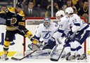 The Boston Bruins' Chris Kelly (left) tries to control the puck in front of Tampa Bay Lightning goalie Mathieu Garon (center) as Victor Hedman (77) and Ryan Shannon (22) defend in the first period of an NHL hockey game in Boston on Saturday. The Bruins won 4-1.