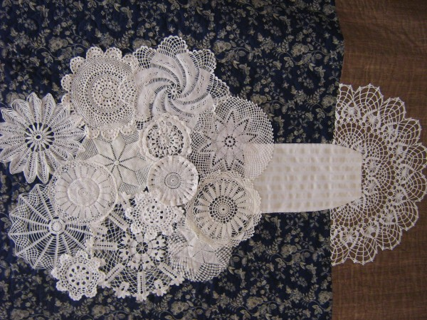 Quilter Carolee Withee created this wallhanging using vintage hand crocheted doilies. Withee hand-colored the lower section, representing a table.