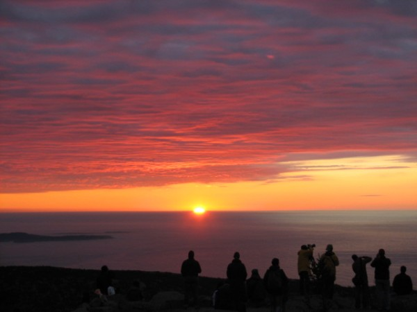 People gather a few minutes before 7 a.m. Saturday, Oct. 22, 2011, at the summit of Cadillac Mountain in Acadia National Park to see the sun rise. Cadillac Mountain is one of three places in Maine that claim to be where the sun first shines in the United States each day, depending on the time of year.