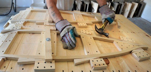 Gary Wozneak hammers wedges along the frame of a Maine Guide snowshoe after he bent the steamed wood. He is one of about seven inmates at the Charleston Correctional Facility who make snowshoe frames from raw material to the finished product. The webbing is later tied onto the snowshoes by veteran in Augusta.
