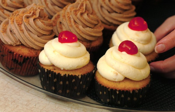 Nicole King arranges freshly baked Pineapple Upside Down cupcakes next to Butterfinger cupcakes in her home-based Cherry Acres Bakery on Wednesday, October 12, 2011.