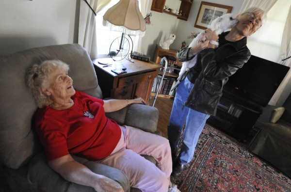 Thelma Lawrence (seated), 84, watches her 2-year-old Maltese, Lily, smooch Gloria DeNicola of Newport during one of DeNicola's regular visits to check up on Lawrence at her home in Madison on Friday, Sept. 30, 2011. DeNicola is a volunteer with the Senior Companion program which is administered by the Cooperative Extension Service.