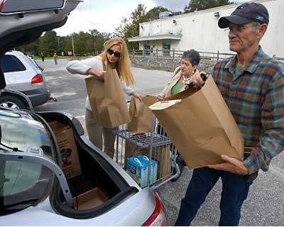 Commissary store bagger Holly Christopher (left) helps Jack and Sandy Davidson with their bags on Wednesday as they shop at the Topsham store for the last time. The store closes Saturday, Oct. 8.