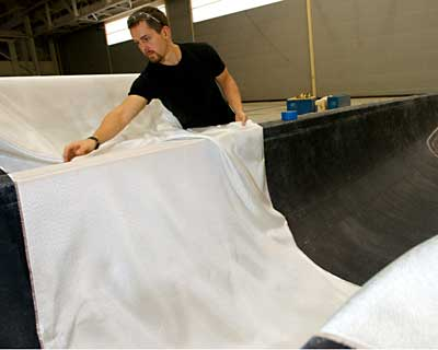 Eric Hinkley of Topsham adds another layer of material to a Kestrel Aviation composite fuselage at their facility at Brunswick Landing.