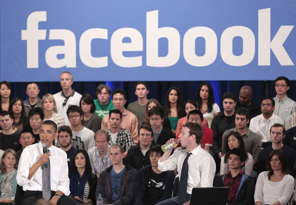 In this April 20, 2011, file photo, President Barack Obama, accompanied by Facebook CEO Mark Zuckerberg, speaks during a town hall meeting to discuss reducing the national debt at Facebook headquarters in Palo Alto, Calif.