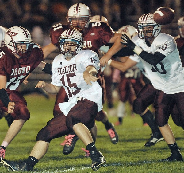 Foxcroft Academy QB Chris Shorey (15), under pressure from Orono's Sam Chase (15), goes for the toss to the backfield in the 1st quarter of their game at Orono, Friday night Sept. 30, 2011.