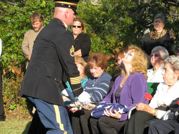 Robyn Campbell takes the folded American flag that had covered the casket of her husband, Don Campbell, Sunday afternoon during his interment ceremony at the Seiders Cemetery in Waldoboro. The pilot for Penobscot Island Air who died Wednesday in a crash on Matinicus was retired from the U.S. Army.