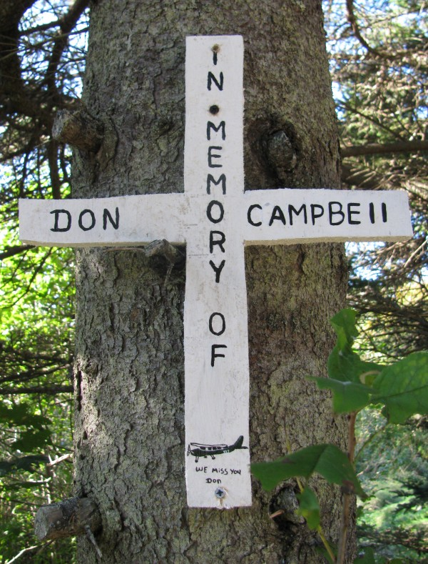 Islander Lacey Leigh made a wooden cross for Penobsot Island Air pilot Don Campbell, hammering it into a spruce tree next to the site where his Cessna crashed Wednesday on Matinicus.