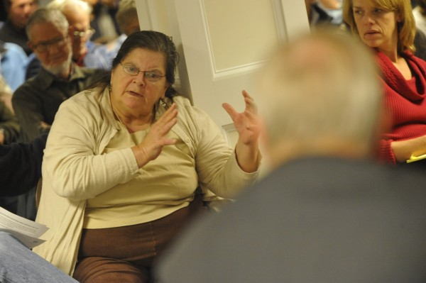 Audience member Elizabeth Worten of Old Town voices her concerns to George MacDonald (in foreground), program manager with the state's planning office, during Tuesday evening's public meeting in Orono regarding the Juniper Ridge landfill expansion proposal.