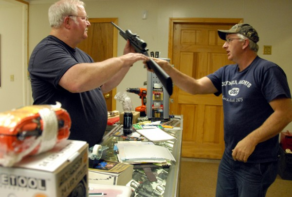 Two Rivers Canoe & Tackle shop owner Barry Davis hands a