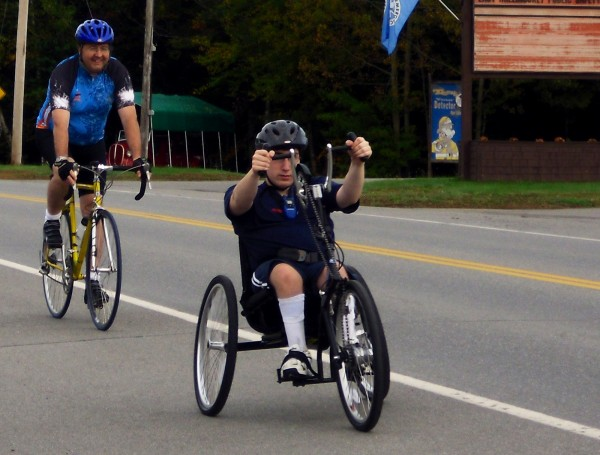 Matthew Jamieson [right] rides a Top End Excelerator Handcycle, a seven-speed three-wheeler with hand pedals built into its steering wheel, past the East Millinocket Public Safety Building during a recent 25-mile jaunt. The 17-year-old Stearns High School junior will attempt to go 50 miles this weekend.
