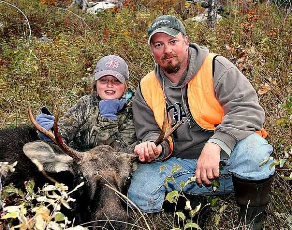 Brian Ellis of Norway crouches next to his 11-year-old daughter, Shyanne, after she shot her first moose on Wednesday in Andover. Father and daughter said they cherish their time together in the Maine woods.