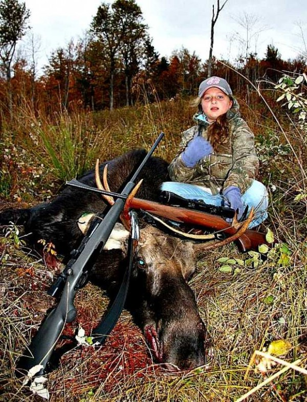 Shyanne Ellis, 11, of Norway, sits with the bull moose she shot Wednesday in Andover with her father, Brian Ellis. It was Shyanne's first harvest. The moose weighs 400 pounds and has a six-point rack.
