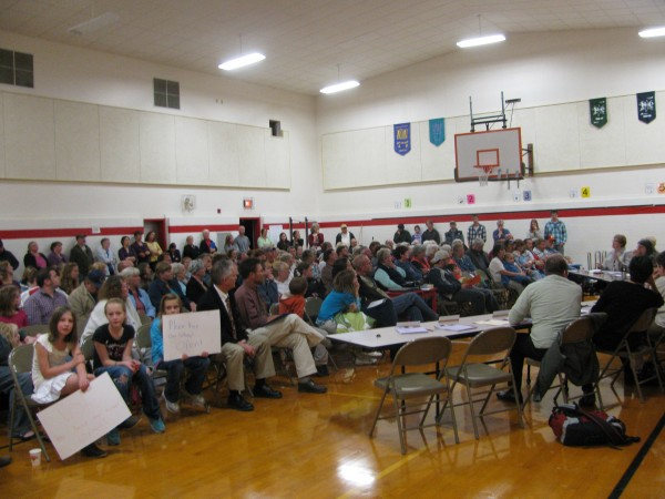 Students held up signs in favor of keeping the Monroe Elementary School open during the RSU 3 School Board meeting Tuesday night. The board voted nine to one to keep it open rather than close it to save about $211,000 annually.