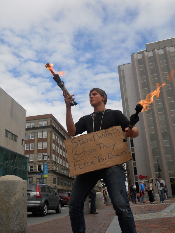 David Bruenjes, 21, of Portland, juggles flaming sticks Monday during the continued occupation of Monument Square organized by Occupy Maine, a group that has sprouted in support of the larger Occupy Wall Street movement.