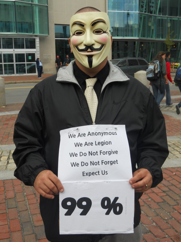 An anonymous member of Occupy Maine holds a sign while wearing a Guy Fawkes mask during the continued occupation of Monument Square by members of Occupy Maine Monday.