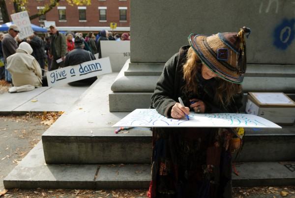 Ina Anahata sits on the Peirce Park monument as she creates a slogan on a sign to be used during the Occupy Bangor parade through the streets of Bangor on Saturday, October 29, 2011.