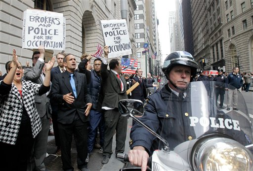 A motorcycle patrolman keeps Occupy Wall Street protesters on the sidewalk as they march down Broadway.