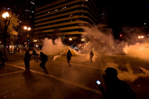Occupy Wall Street protesters run from tear gas deployed by police at 14th Street and Broadway in Oakland, Calif. on Tuesday.