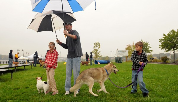 Lucas Fowler of Dexter stands in the rain with his children Kelsey, 8, and Caleb, 6, as they were awaiting the start of the 18th annual Paws on Parade at the Bangor Waterfront Saturday.