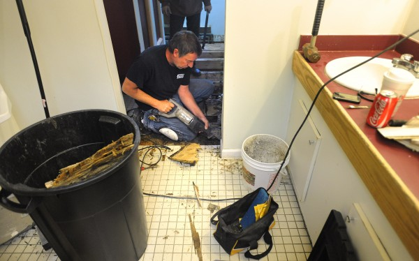 Paul Laffey with the Old Town-based GWK Construction works on replacing the subfloor in one of the bathrooms at the Pi Kappa Alpha fraternity house in Orono in October 2010.