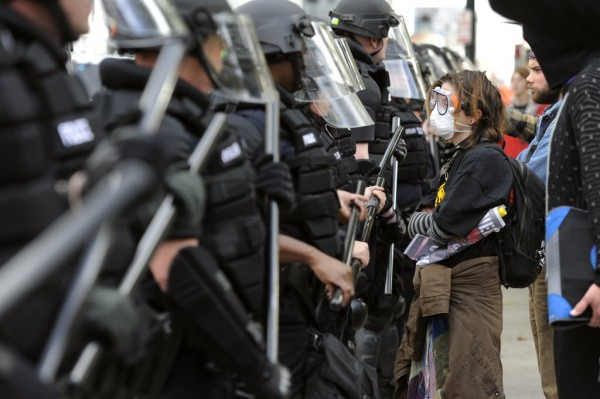 Elaina Jeansonne stands in front of police during the Occupy Denver protest, Saturday in Denver.