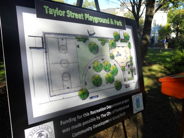 A plan for renovations to a park and playground on Taylor Street stands after a groundbreaking ceremony Thursday afternoon while kids swing on the current playground equipment in the background.