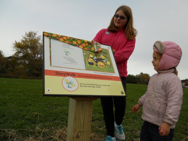 Abigail DeLuca, 12, and Zoe Murray, 4, unveil one of the storyboard panels in Portland's new StoryWalk, in which pages of the children's book &quotThe Bugliest Bug&quot lead kids along a path in Payson Park.