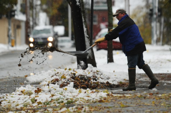 Greg Jones shovels melting snow and leaves from the entrance to his residence on Center Street in Bangor on Sunday, Oct. 30, 2011.