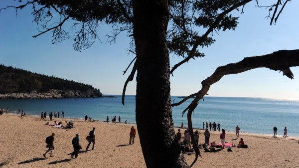 People enjoy a sunny day on Sand Beach in Acadia National Park on Monday. The unusally warm weather attracted a large number of tourists to the usual sightseeing and vacation spots in Maine.