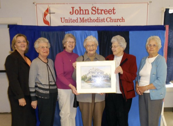 Holding a painting of Sixty-Three Washington Street in Camden are Georgie McMichael, Mary Jane Gautesen, Judy McKearney, Priscilla Hart, Kay Moody and Teddy Wilcox, all volunteers at the facility for senior citizens. The John Street United Methodist Church in Camden will welcome Northern Breeze performing gospel music at 6:15 p.m. Saturday, Nov. 5, at the church as a fundraiser for Sixty-Three. The concert will be preceded by a baked bean supper at 5:30 p.m. The cost of the supper is $7. Northern Breeze will not charge admission, but will request donations to benefit Sixty-Three Washington Street, an assisted living facility in Camden that has housed seniors for more than a century. The event is open to all.
