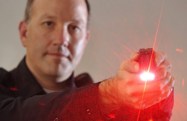 Jason McAmbley, community relations officer for the Bangor Police Dept., demontrates the laser sight on on of the department's Taser guns.