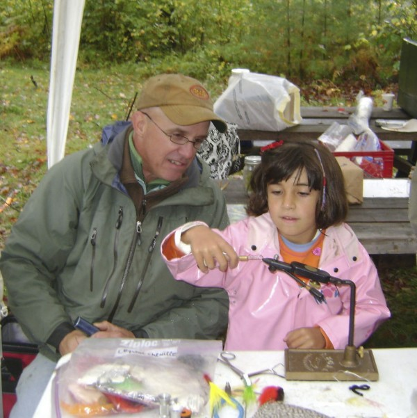 Sean McCormick assists Halena Stone in fly-tying at a recent Hidden Valley Nature Center event in Jefferson.
