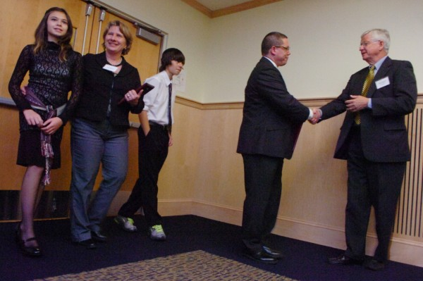 Nicole Maines (left), 14, her mother, Kelly Maines, and her twin brother, Jonas, listen to applause as Maine ACLU president John Paterson (right) shakes hands with Wayne Maines after the family received the Maine ACLU's 2011 Roger Baldwin Award in Orono on Thursday evening, Oct. 27, 2011.