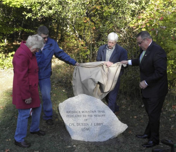 A monument to marine Cpl. Dustin J. Libby, who was killed in Iraq five years ago, was dedicated Friday at the head of the summit trail to Haystack Mountain in Castle Hill. Unveiling the trail head marker are (from left) Libby's mother Geni, brother Chris and father Judd, with Gov. Paul LePage.