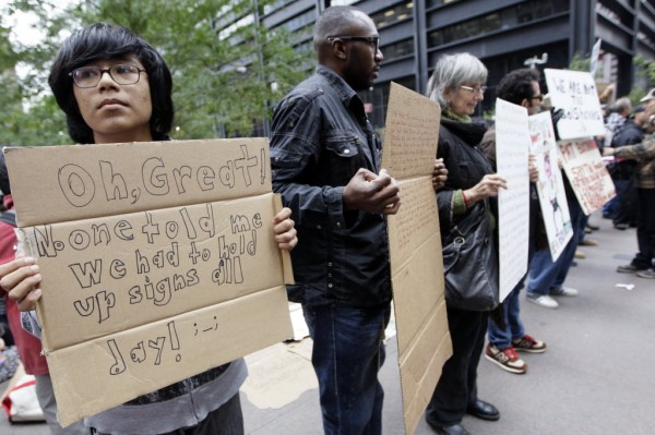 Pedro Gutierrez, 17, left, holds a sign standing next to other demonstrators at the Occupy Wall Street encampment in Zuccotti Park, Friday, Oct. 21, 2011 in New York.