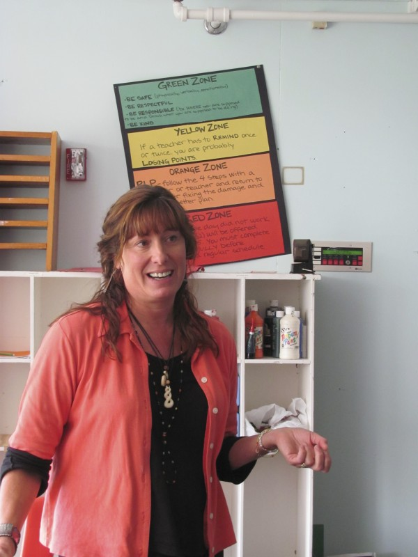 Pender Makin, director of The Real School in Falmouth, describes how the school deals with behavior problems to a group of University of Southern Maine graduate students on Tuesday, October 11, 2011. Behind her is a poster that shows the school's color-coded system of how a student is expected to deal with his or her own behavior.