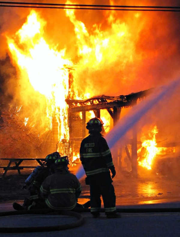 Members of the Mexico Fire Department work to put out a house fire at 300 River Road in Mexico on Tuesday night. Residents were able to escape minutes before their house was completely engulfed in flames. Two cars were inside the car port during the blaze. Lisa Malchisky said she could hear them exploding from across the street.