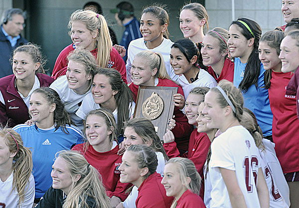 The Bangor girls soccer team celebrates with its Eastern Maine Class A girls soccer championship trophy Wednesday after defeating Brunswick 2-0 at Husson University's Boucher Field.