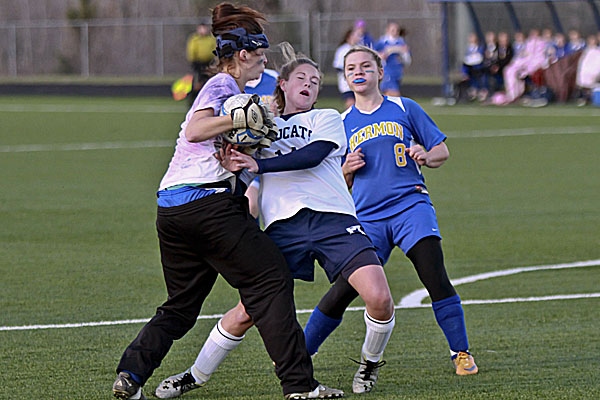 Hermon High School goalkeeper Mikayla Treadwell latches onto the ball just ahead of a hard-charging Chandler Guerrette of Presque Isle in Wednesday's Eastern Maine Class B girls soccer semifinal at the University of Maine-Presque Isle's Johnson Athletic Complex. Hermon's Amanda Allen looks on. Guerrette scored both goals in the the Wildcats' 2-0 victory.
