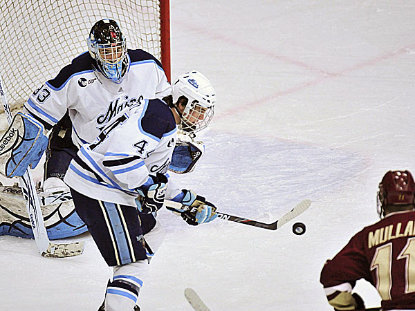 Maine defenseman Ryan Hegarty uses his stick to stop a puck in front of goalie Shawn Sirman while Boston College's Pat Mullane looks on during a game last season. The Maine defense will be tested this weekend when the Black Bears play BC and New Hampshire.