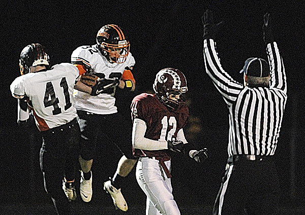 Brunswick's Hunter Ouellette (41) and Jarod Jensen (32) celebrate after Jensen scores in the first quarter of Friday night's Eastern Maine Class A football semifinal at Cameron Stadium in Bangor. Bangor's Carl Farnham (12) is on right.