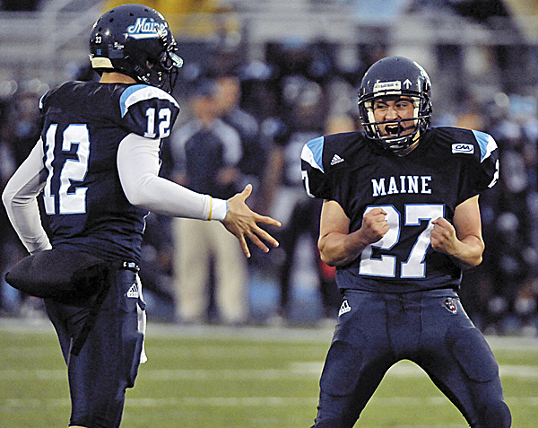 Backup quarterback Chris Treister (left) of the University of Maine congratulates teammate Brian Harvey after Harvey's extra-point kick in Orono against Delaware. Treister has accepted his role with the team after battling for the starting QB job for three years.