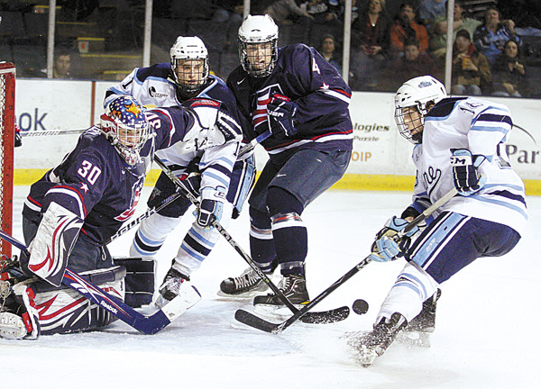 Jon Swavely (right) of the University of Maine can't connect as he tries to put in the rebound of a shot saved by Matt McNeely (left) of the U.S. Under-18 team Sunday, Jan. 2, 2011. The Black Bears' Theo Andersson (second left) and USA's Michael Paliotta look on. UMaine won 5-1. The teams square off again Wednesday at Alfond Arena in Orono.