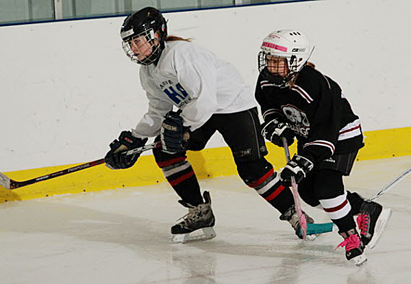 Natalie Whitehead (right), chasing the puck along with a Houlton opponent, is a Bangor Youth Hockey girl who could be a candidate to play if one or more Bangor-area high school girls hockey teams are started.
