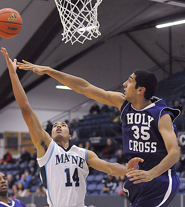 Holy Cross's Eric Obeysekere (right) tries to block a shot by the University of Maine's Justin Edwards during the firs half in Orono Sunday afternoon.