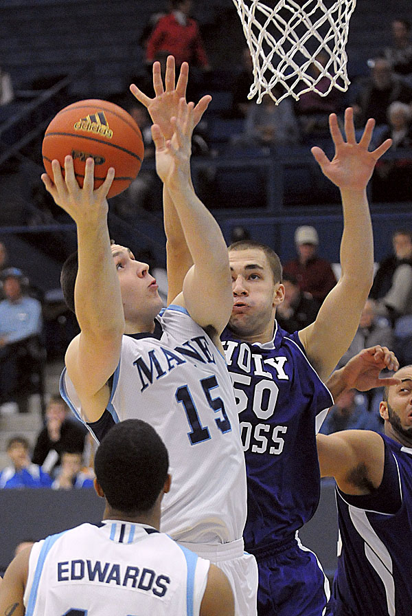 The University of Maine's Alasdair Fraser (15) goes up for a shot against Holy Cross's  Dave Dudzinski during the first half in Orono Sunday afternoon.